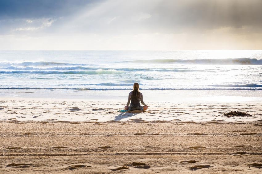 William Holsinger - Styles of Meditation - A woman meditating at a beach.